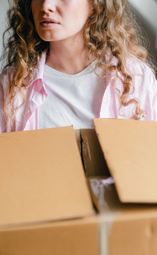 crop-serious-young-lady-carrying-carton-box-at-home