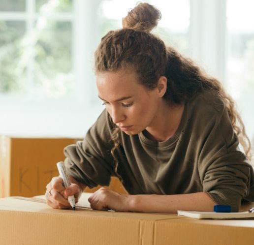 focused-woman-signing-boxes-with-packed-stuff