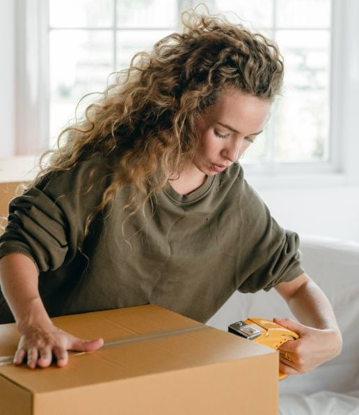 focused-young-woman-packing-carton-boxes-with-adhesive-tape