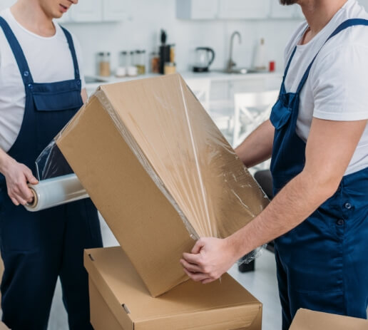 partial-view-of-movers-wrapping-cardboard-box